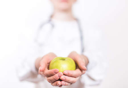 Young smiling woman brunette doctor wearing glasses and a medical white lab coat with a stethoscope holds on a stretched out hand a green apple on a white background Фото со стока