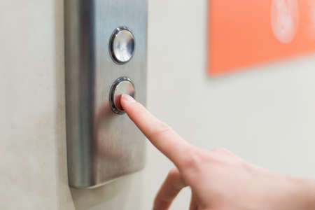 Closeup portrait of a female finger pushing elevator button