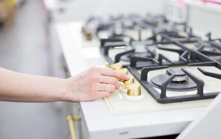 Frustración segura con el fuego. Estufa de cocina moderna cocinar con llamas azules ardiendo y mano de mujer