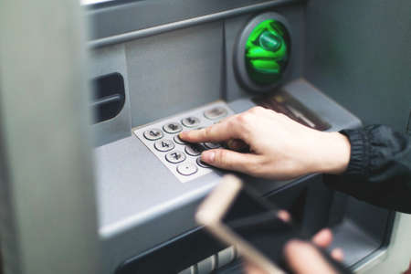 Closeup of female hands using smart phone while typing on ATM, bank machine