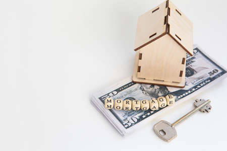 mortgage, loan and home purchase. Model of house, dollar bills, key on white isolated background. Free space for text