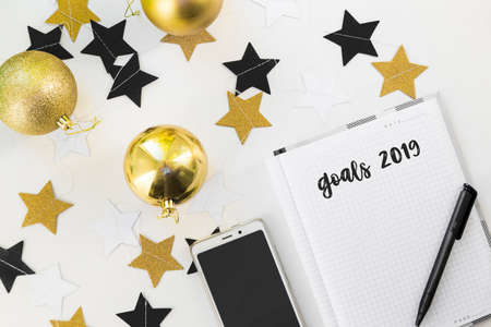 Happy New Year's layout. numbers 2019 notepad and free space for text. Christmas decorations, Christmas toys, gold stars. Goals for the new year. mock up mobile phone