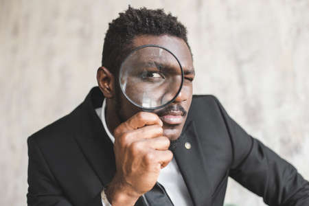 Enlarged eye of African American tax inspector looking through magnifying glass, inspecting offshore company financial papers, documents and reports.