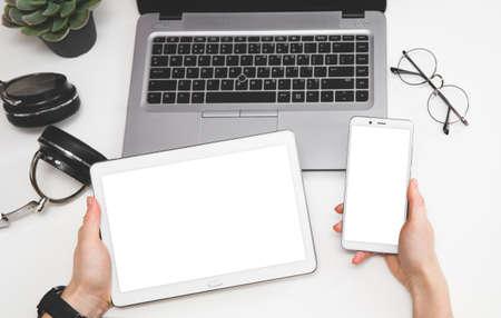 Responsive design mockup. Mock up mobile phone, digital tablet and laptop. Woman hands on office desk