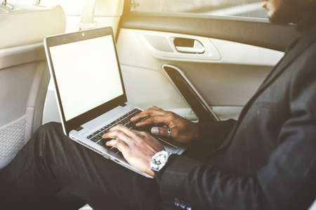 African American man sitting in the back seat of an expensive car with leather interior and working at a laptop, business talks. Mockup screen,