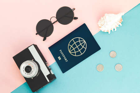 Flatlay traveler accessories on blue background with palm leaf, camera, international passport and sunglasses. Top view travel or vacation concept. Summer background.