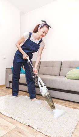 Servicio de limpieza con equipo profesional durante el trabajo. Professional limpieza en seco de alfombras, limpieza en seco de sofás, lavado de ventanas y suelos. mujeres en uniforme, overoles y guantes de goma.
