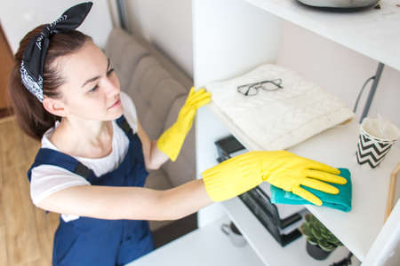 Cleaning service with professional equipment during work. professional kitchenette washing, sofa dry cleaning, window and floor washing. women in uniform, overalls and rubber gloves. Archivio Fotografico