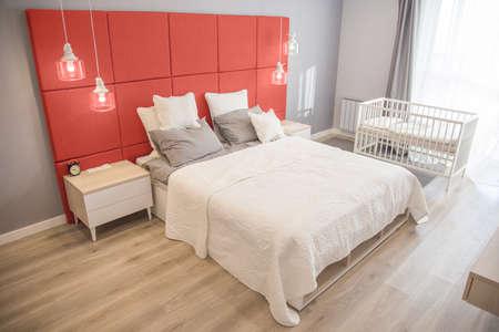 Interior de la habitación en colores claros. Dormitorio con cama y cuna en colores del año 2019 Coral vivo