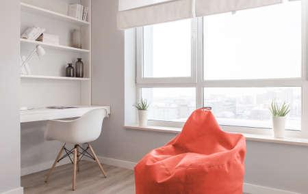 Interieur van het appartement. Ontwerp van de kamer in Scandinavische stijl, werkplek bij het raam in kleuren van het jaar 2019, levend koraal. Stockfoto