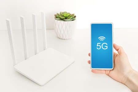 Woman hold smartphone near wi-fi router with 5g. Stok Fotoğraf