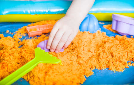 The hands of a child girl playing with kinetic sand. development of fine motor skills Imagens