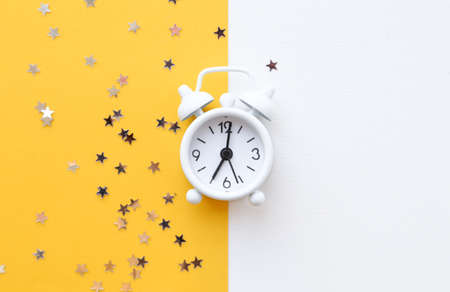 White table clock, alarm on yellow background, top view. Good morning. Minimalism, flatlay