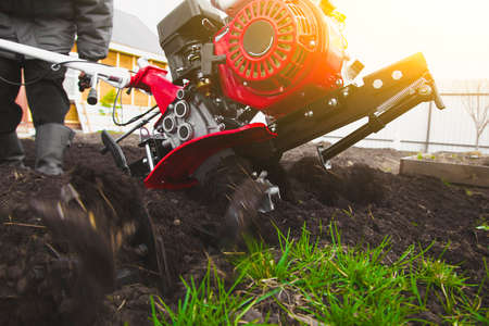 A man is a farmer plowing the land in the garden with a hand tractor cultivator. Stock Photo