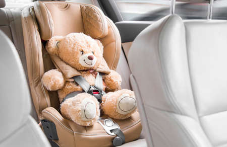 A beige teddy bear is fastened with seat belts in a car seat. Travel by car Imagens