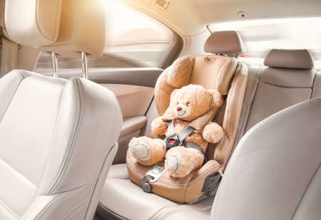 A beige teddy bear is fastened with seat belts in a car seat. Travel by car Reklamní fotografie