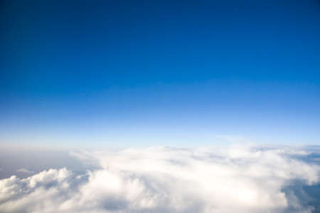 Blue sky with white clouds during the afternoon. view from the airplanes illuminator. copy space for text