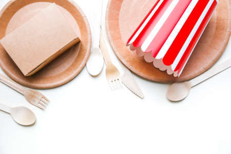 eco friendly disposable dishes made paper on white marble background. Draped spoons, fork, knives, plate with paper cups. recycling concept. Banco de Imagens