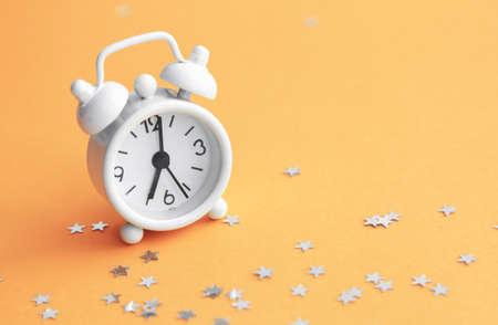 White table clock, alarm on yellow background, top view. Good morning. Minimalism, flatlay. Banco de Imagens