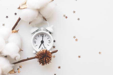White table clock, alarm on white background, top view. Good morning. Minimalism, flatlay.