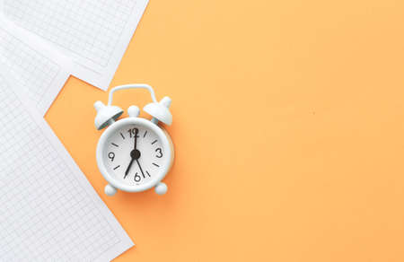 White table clock, alarm clock on a bright background, top view. Break at work in the office. Paper. Banco de Imagens