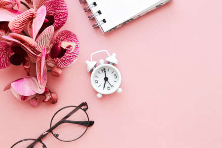 White table clock, alarm clock on a bright background, top view. Break at work in the office. Paper, flatlay. Banco de Imagens
