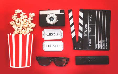 Cinema party concept. movie tickets, clapperboard, pop corn and 3d glasses in a red