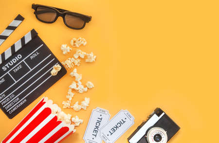 Cinema party concept. movie tickets, clapperboard, pop corn and 3d glasses in a yellow