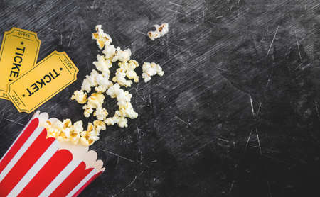 Cinema party concept. movie tickets, clapperboard, pop corn and 3d glasses in a black