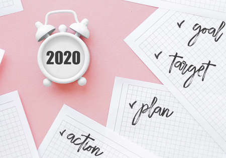 new goals for 2020. Composition flat lay. alarm clock on pink background. Stock Photo