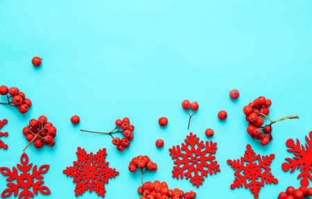 Winter composition. Frame made of snowflakes and red berries Rowan on pastel blue background. Christmas, winter, new year concept. Flatlay, top view, copy space.