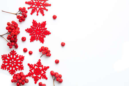 Winter composition. Frame made of snowflakes and red berries Rowan on white isolated background. Christmas, winter, new year concept. Flatlay, top view, copy space.