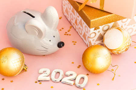 Christmas composition on a pink background. Boxes with gifts and the symbol of the Chinese New Year 2020 - Rat. 写真素材