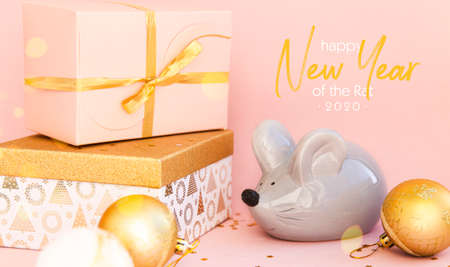 Christmas composition on a pink background. Boxes with gifts and the symbol of the Chinese New Year 2020 - Rat Banner.