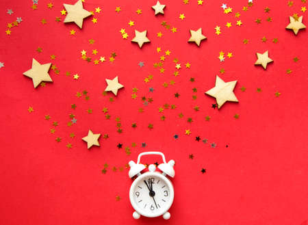 Flat lay composition. Alarm clock and Christmas decorations on red background. top view, copy space. 写真素材