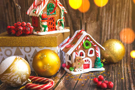 Gingerbread candy house, Christmas accessories and decorations on wood background