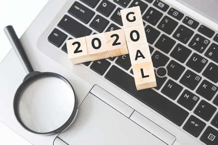 Search 2020 goal concept, Hand flip wood cube change the word on lantop, magnifier.