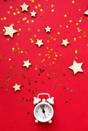Alarm clock and Christmas decorations on red