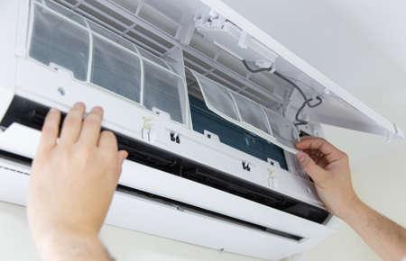 Técnico de sexo masculino que limpia el aire acondicionado en interiores. Foto de archivo