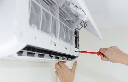Male technician cleaning air conditioner indoors.