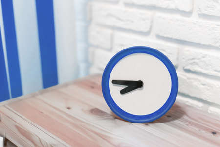 Alarm clock next to sockets and switches in colors 2020 classic blue