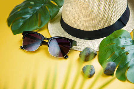 straw hat and sunglasses on a background of palm leaves. Creative tropical summer travel top view layout. Flat lay. Vacation concept