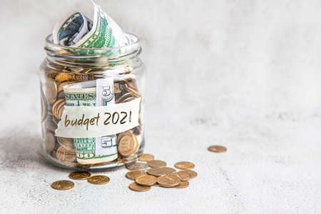 Budget 2021. Glass jar with money, coins and notes, savings, loans and mortgages.