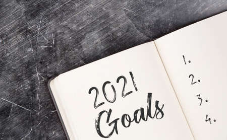 2021 on the office desk in a notebook. Plans and goals for the new year. Top view layout on white background. Reklamní fotografie