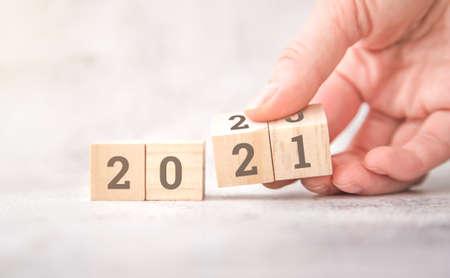 women hands hold wooden cubes 2021. new goals for next year