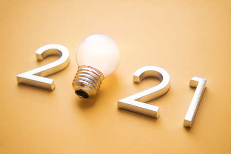 metal numbers 2021 with a burning light bulb. New ideas in the new year