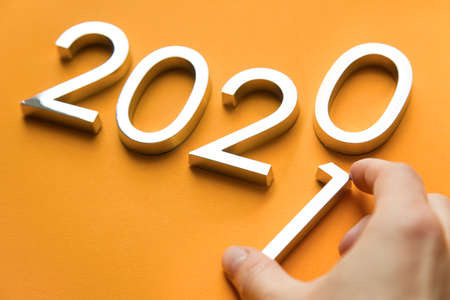 Close-up of metal numbers 2021 and hand on orange background. change year 2020 to 2021