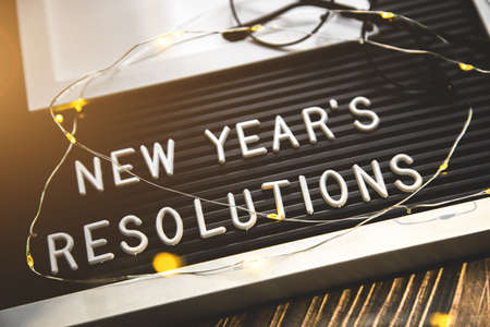 List of resolutions for new year. sign with letters and garland