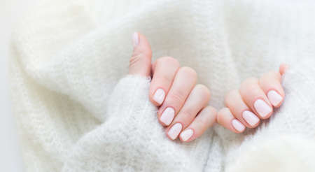 well-groomed female hands after manicure on the background of a knitted sweater. Pastel varnish on the nails