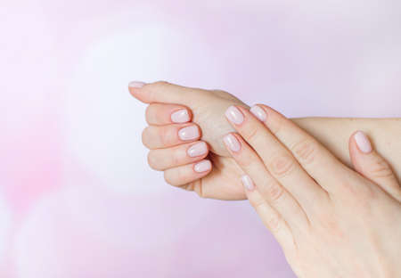 well-groomed female hands after manicure on the pink background. Pastel varnish on the nails Zdjęcie Seryjne